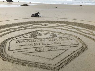 Drawing in sand of Bandon Wayside Motel + RV logo with dog lying on sand