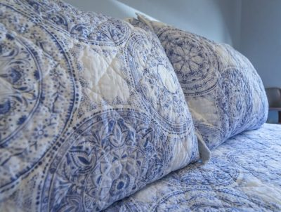 detailed image of bed with blue and white linens