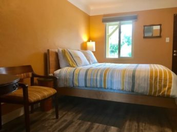 bedroom with yellow walls and comfy bed with chair
