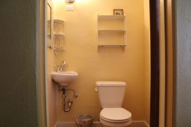 Bathroom with corner sink and shelving