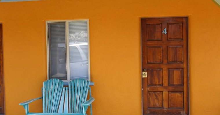Exterior view of Room 4 with bright orange walls and blue chair.